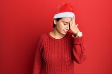 Beautiful Young Woman With Short Hair Wearing Christmas Hat Surprised With Hand On Head For Mistake, Remember Error. Forgot, Bad Memory Concept.