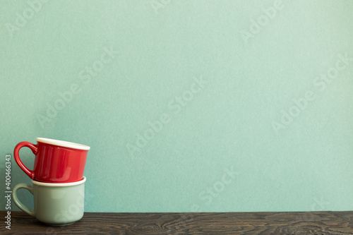 Fotografia Stack of ceramic mug cups on wooden table. green background