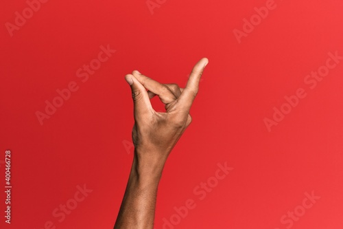 Foto Hand of hispanic man over red isolated background snapping fingers for success,