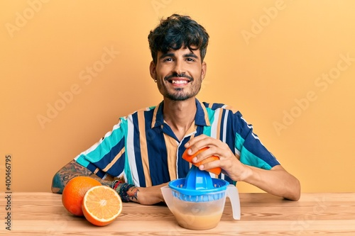 Young hispanic man sitting on the table using juicer looking positive and happy Wallpaper Mural