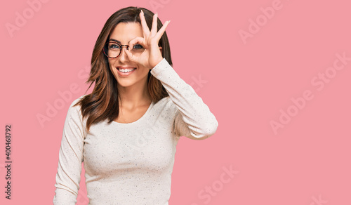 Obraz Young brunette woman wearing casual clothes and glasses doing ok gesture with hand smiling, eye looking through fingers with happy face. - fototapety do salonu