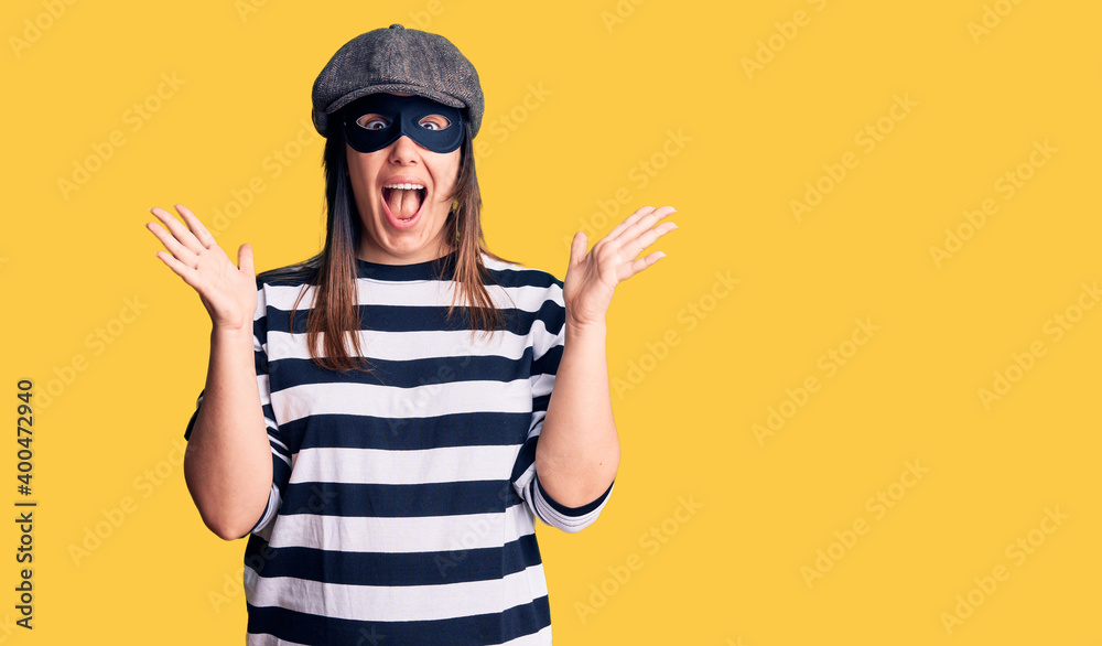 Fototapeta Young beautiful brunette woman wearing burglar mask celebrating crazy and amazed for success with arms raised and open eyes screaming excited. winner concept