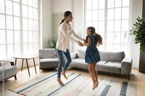 Obraz Overjoyed young mother and little daughter dancing, moving to music in living room, family enjoying leisure activity, happy mum and adorable girl child holding hands, jumping, having fun together - fototapety do salonu