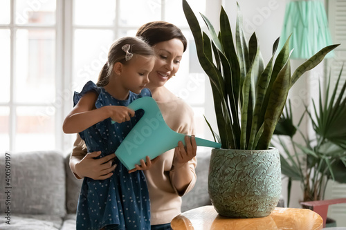 Fotografia, Obraz Smiling mature grandmother teaching little granddaughter to watering plant, hold