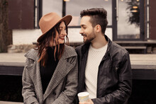 Heterosexual Satisfied Married Couple Have A Date Outside Near Cafe On Pier. Drinking Hot Chocolate Coffee Beverage And Hugging, Kissing, Speaking Laughing, Spend Time. Romantic Lovers Husband Wife