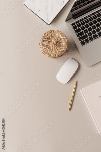 Obraz Home office desk workspace with laptop, straw casket on neutral background. Flat lay, top view blog, website, social media concept. - fototapety do salonu