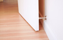 Stainless Door Stopper With White Door And White Wall ,selective Focus
