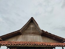Wooden Attic In Southeast Asia. Against A Clear Sky Backdrop