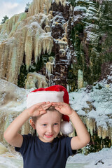 Boy in red Santa Claus hat is smiling