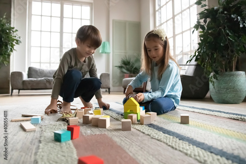 Obraz Close up little girl and boy playing with colorful wooden blocks and toy dinosaurs, sitting on warm floor with underfloor heating, curious cute sibling having fun at home together, enjoying weekend - fototapety do salonu