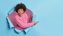 Excited Cheerful Curly Woman Gazes At Camera With Very Happy Expression Smiles Broadly Points At Right Side Advertises Copy Space Wears Pink Knitted Sweater Breaks Through Blue Paper Background