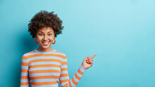 Cheerful Young Afro American Woman Shows Free Place For Mockup Demonstrates Invisible Object Smiles Positively Stands Over Blue Background Wears Striped Jumper. People And Promotion Concept.