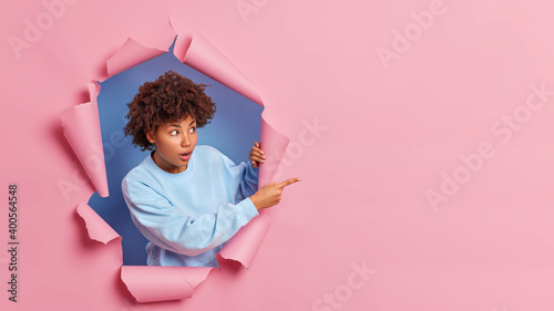 Fotografie, Obraz Shocked dark skinned woman with Afro hair advertises wonderful item has stunned face expression looks with great wonder at right side wears blue sweater poses in ripped paper hole