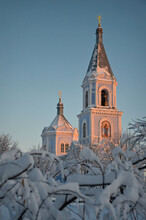 Church At Sunset Among The Trees In The Snow. Beautiful Russian Winter. Bell Tower Of The Orthodox Church.