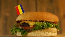 Delicious Burger With Small Romanian Flag On Top Of Them With Toothpicks. Yummy Hamburger Rotating.