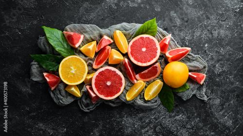 Obraz na plátně Fresh citrus fruits on black stone background