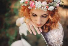 Beautiful Young Red-haired Bride In The Forest With A Floral Wreath On Her Head And Mirror . Woman In Long White Dress Outdoors On Summer Day. Wedding Day