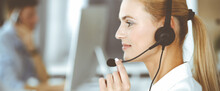 Blonde Business Woman Using Headset For Communication And Consulting People At Customer Service Office. Call Center. Group Of Operators At Work