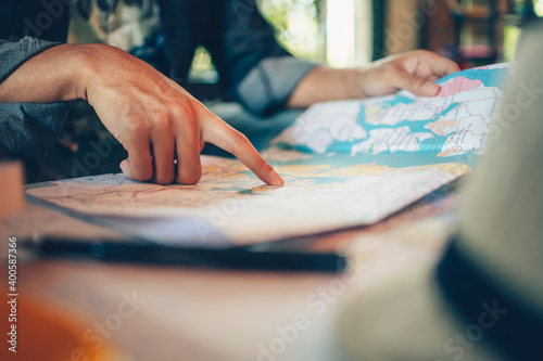 Fotografie, Obraz Close-up Tourist planning vacation with map and other travel accessories on the table