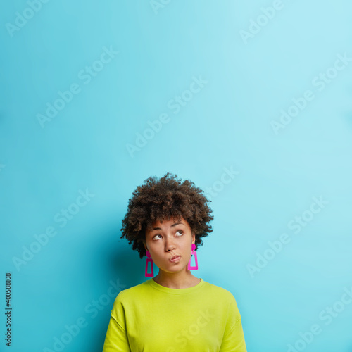 Pensive dark skinned woman purses lips and looks above thinks about something concentrated upwards with thoughtful expression wears earrings and t shirt isolated over blue background empy space