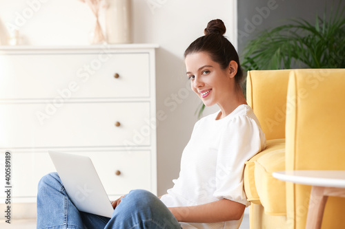 Fototapeta Young woman with laptop at home