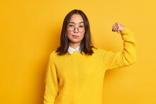 Photo Of Serious Brunette Asian Woman Raises Arm And Shows Her Strength Has Strong Muscles Stands Self Confident Indoor Wears Yellow Sweater And Round Optical Spectacles. Women Power Concept