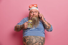 Serious Bearded Man With Big Fat Tattooed Belly Wears Snorkeling Goggles And Sailor Striped Jumper Drinks Fresh Water Has Telephone Talk Poses Against Pink Background. People Leisure Lifestyle Concept
