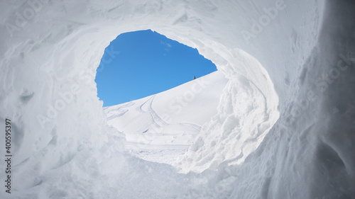 view out from snow cave into winter landscape and blue sky