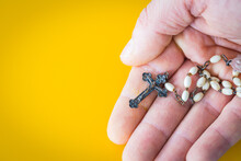 Hand-held Christian Rosary. Yellow Background. Place For Text