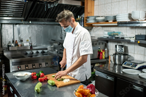 Canvas Professional young chef in uniform and protective mask cooking by large table