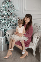 A Mother In A Pink Dress Sits With Her Daughter In A White Chair Next To A Christmas Tree In A Room