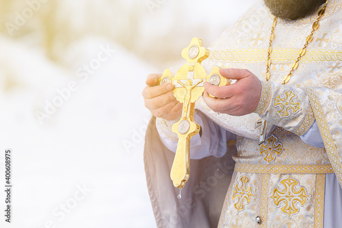 Fotografie, Tablou The hands of a priest dip an Orthodox gold cross into the river