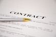 the pen is on the contract and the contract is on a white background