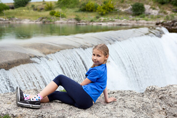 Portrait of pre-teen girl resting close to waterfall of the Cijevna river. It is called Montenegrin Niagara Falls. Surroundings of Podgorica city. Montenegro, Europe