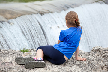 Rear view at preteen age girl sitting on edge of waterfall of the Cijevna river. It is called Montenegrin Niagara Falls. Surroundings of Podgorica city. Montenegro, Europe