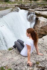 Pretty woman sitting on rock and enjoying of the cascade of Cijevna river. It is called Montenegrin Niagara Falls. Surroundings of Podgorica city. Montenegro, Balkans, Europe