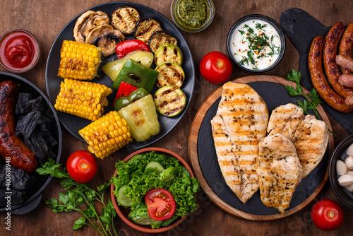 Obraz na plátně Grilled sausages, meat, and vegetables.