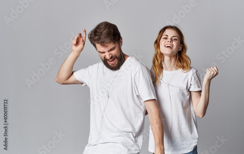 Obraz cheerful man and woman in headphones listen to music and dance on a gray background - fototapety do salonu
