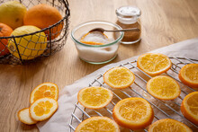 Candies Oranges Concept: A Basket Of Citrus Fruits, A Bowl Of Sugar With An Orange Slice And A Spoon, Gingerbread Spice Mix, And Orange Slices Drynig On A Rack With Parchment Paper, On A Wooden Table.