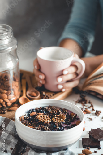 Fototapeta Healthy breakfast, muesli with berries and orange juice served on glass table and books. manicure obraz