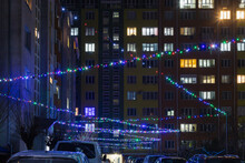 The Night Courtyard Of Multi-storey Apartment Buildings Is Decorated With A Luminous Garland