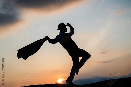 Leinwand Poster silhouette of male dancer dance in sense of freedom on sunrise sky, inspiration