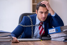 Chained Male Employee Unhappy With Excessive Work In The Office