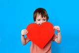 Portrait of stylish little boy holding big red heart blue background