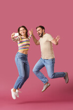 Jumping Young Couple Taking Selfie On Color Background