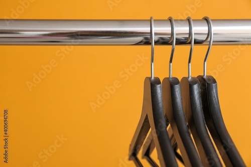 Obraz na plátně Rack with clothes hangers on color background, closeup