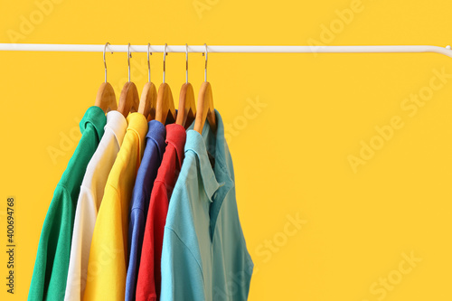Fototapeta Rack with clothes on color background