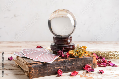 Spell book, crystal ball and cards on wooden table Fototapeta
