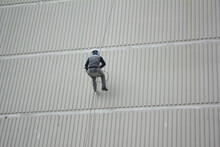 Working Man On The High Building . Building Maintenance Cleaning And Paint The Exterior Of The Building Wall.