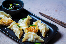 Fried Gyoza Dumplings With Sauce And Green Onions On Black Plate, Dark Background. Japanese Cuisine Concept.